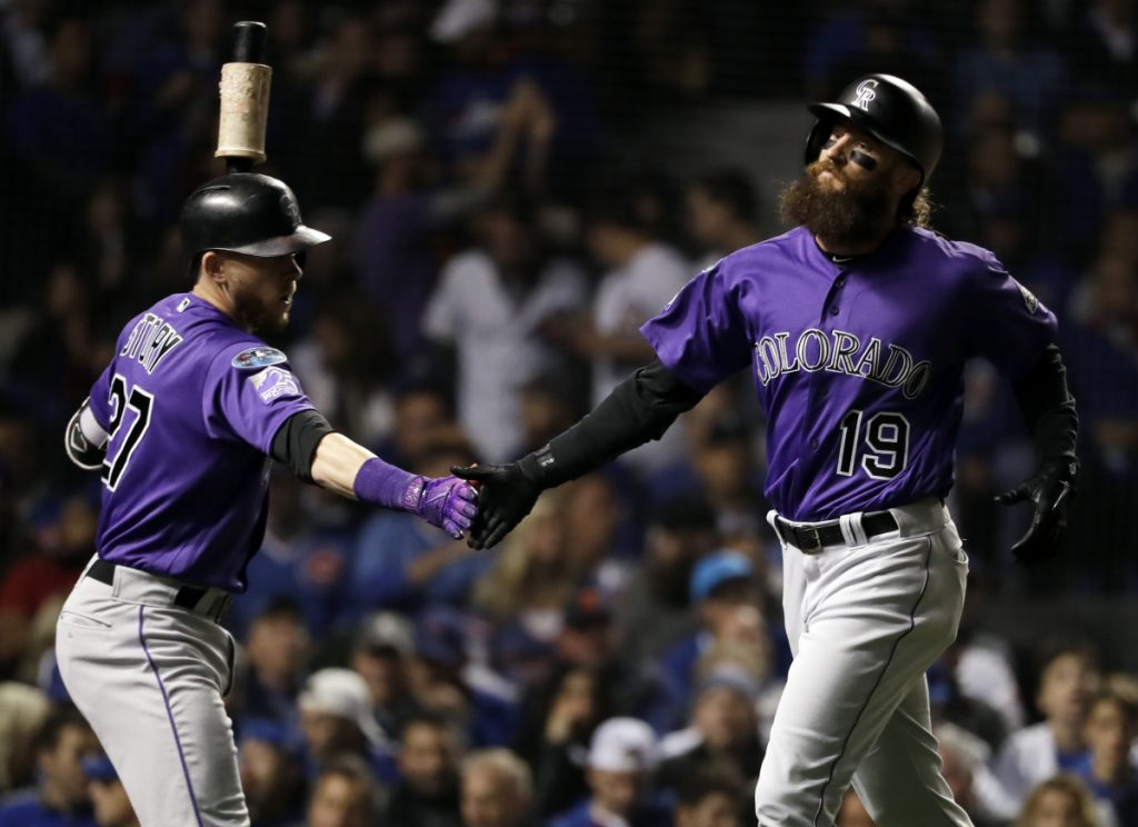 Colorado's Charlie Blackmon, right, celebrates with Trevor Story after scoring on a sacrifice fly by Nolan Arenado against the Chicago Cubs on Tuesday night.