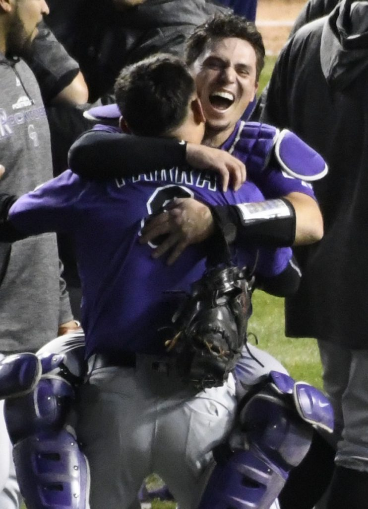 Rockies catcher Tony Wolters, rear, and left fielder Gerardo Parra celebrate Tuesday's 13-inning win at Chicago.