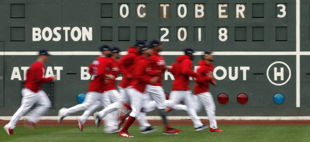 Red Sox players jog in the outfield during a workout at Fenway Park on Wednesday. The Red Sox will host Game 1 of the American League Division Series on Friday night against the Yankees or Athletics.