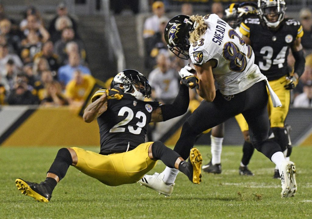 Steelers cornerback Joe Haden, left, stumbles as he tries to tackle Baltimore receiver Willie Snead. Pittsburgh's defense as a whole has also slipped, ranking in the bottom third in the league.
