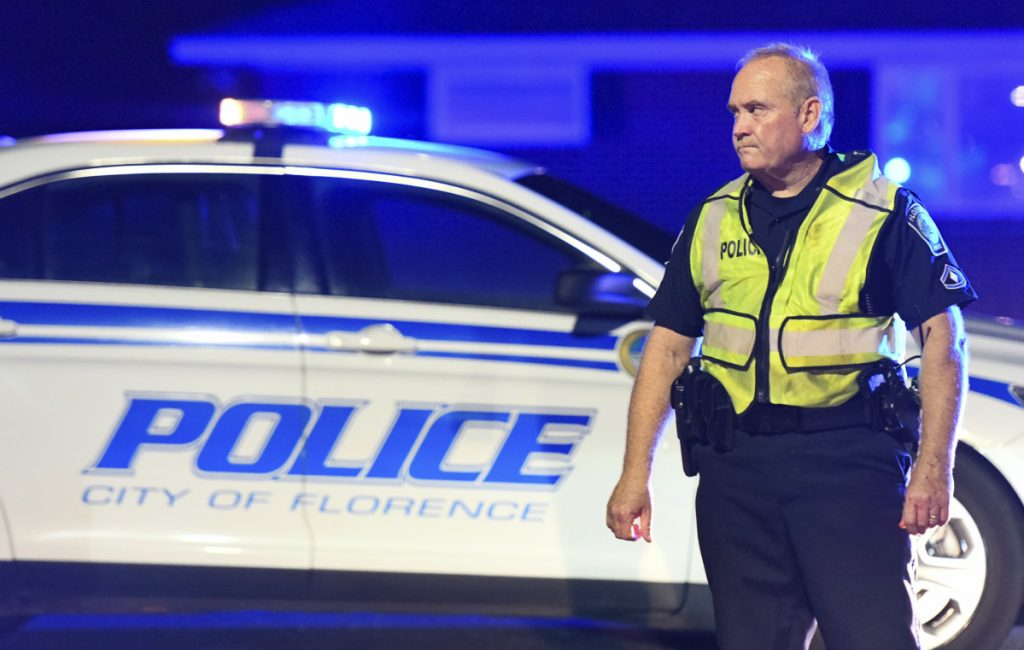 A police officer directs traffic on Hoffmeyer Road near the Vintage Place neighborhood where three deputies and four city officers were shot Wednesday in Florence, S.C.
