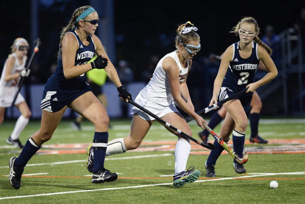 Biddeford's Abby Allen splits Westbrook defenders Avery Tucker, left and Abigail Symbol, in Friday's field hockey showdown at Biddeford. Allen scored one of the goals in the Tigers' 2-0 win.