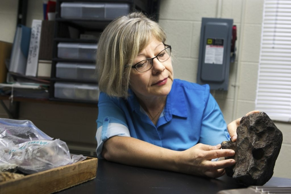 Monaliza Sirbescu, a geology faculty member in earth and atmospheric sciences, shows off a meteorite that was being used as a doorstop on a farm in Edmore, Michigan.