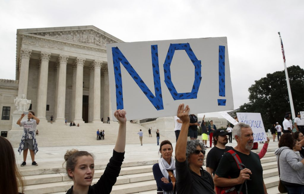 Activists demonstrate in front of the Supreme Court to protest the confirmation vote of Supreme Court nominee Brett Kavanaugh on Capitol Hill on Saturday.