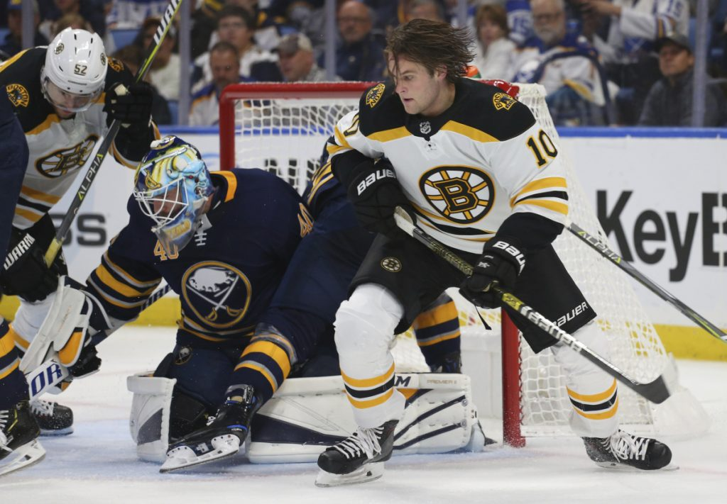 Boston forward Anders Bjork looks for the loose puck after losing his helmet in front of Buffalo Sabres goalie Carter Hutton on Thursday in Buffalo N.Y.