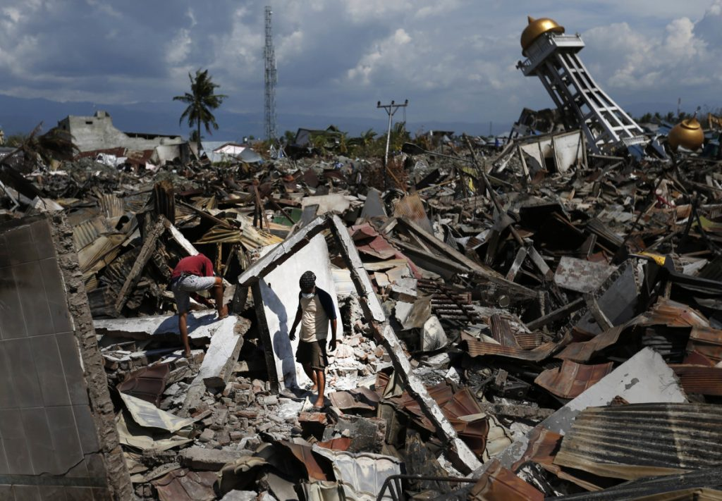 Residents search for salvageable items in their quake-stricken neighborhood in Palu, Sulawesi, Indonesia, on Saturday. Two obliterated neighborhoods may be turned into mass graves.