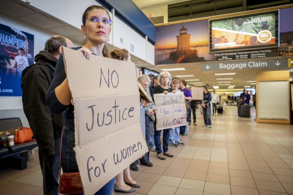 Delina Malo-Juvera holds a sign Sunday at the Portland International Jetport.