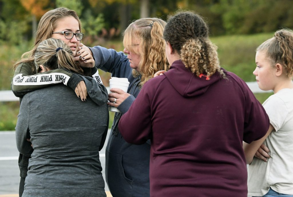 Friends of victims who died in Saturday's fatal limousine crash comfort each other after placing flowers at the intersection in Schoharie, N.Y., Sunday, Oct. 7, 2018. A limousine loaded with revelers headed to a 30th birthday party blew a stop sign at the end of a highway and slammed into an SUV parked outside a store, killing all people in the limo and a few pedestrians, officials and relatives of the victims said Sunday.