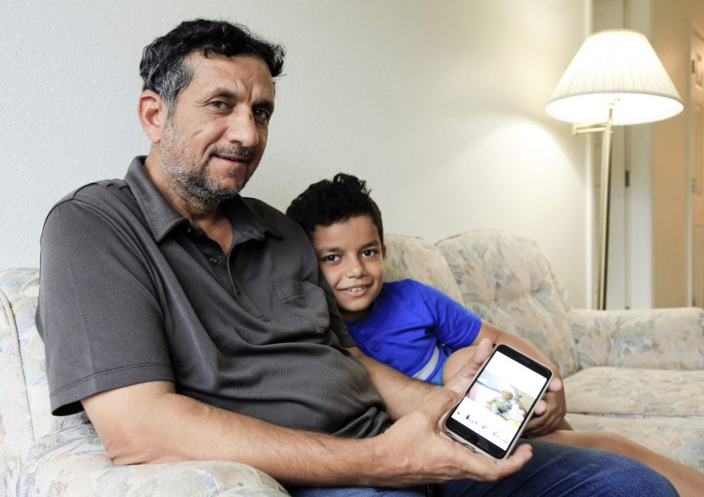 Hadi Mohammed sits with his 9-year-old son Mohammed Ghaleb, as he displays a photo of his son as a baby in Baghdad, in their Lincoln, Neb. apartment. Death threats drove Hadi Mohammed out of Iraq and to a small apartment in Nebraska, where he and his two young sons managed to settle as refugees. But the danger hasn't been enough to allow his wife to join them.
