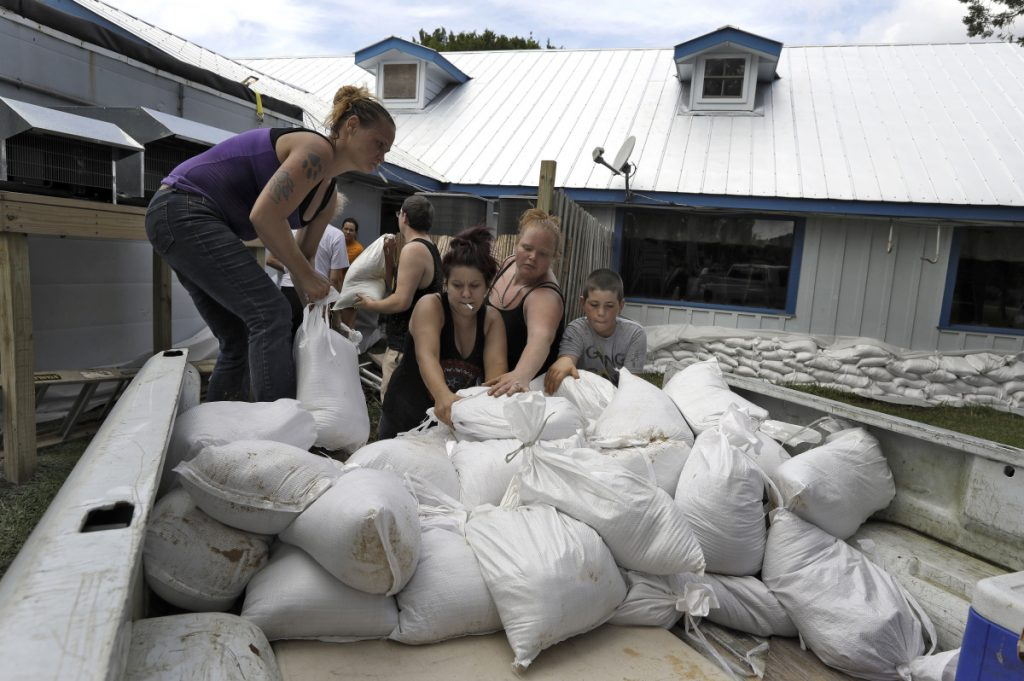 Krystal Day, of Homosassa, Florida, left, leads a sandbag assembly line at the Old Port Cove restaurant Tuesday in Ozello, Florida. Employees were hoping to protect the restaurant from floodwaters as Hurricane Michael continues to churn in the Gulf of Mexico heading for the Florida Panhandle.