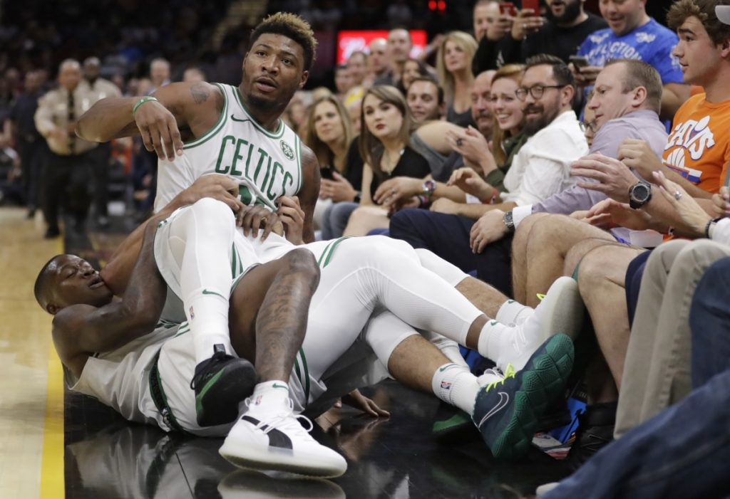 Marcus Smart of the Celtics is held back by teammates during an NBA preseason game Saturday night at Cleveland. Smart was defending a teammate and got ejected for butting in and fined $25,000.