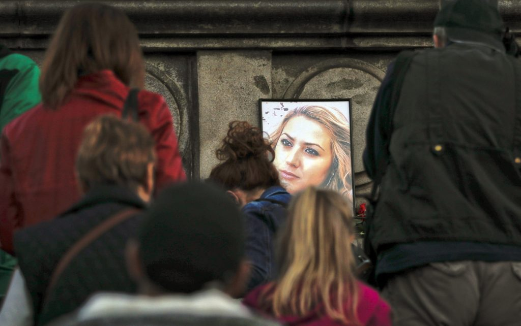 A portrait of slain television reporter Viktoria Marinova, above, is placed on the Liberty Monument in Ruse, Bulgaria, as people attend a vigil on Monday. At left, a member of the Human Rights Association Istanbul branch, holds a poster with a photo of missing Saudi journalist Jamal Khashoggi, during a protest on Tuesday.