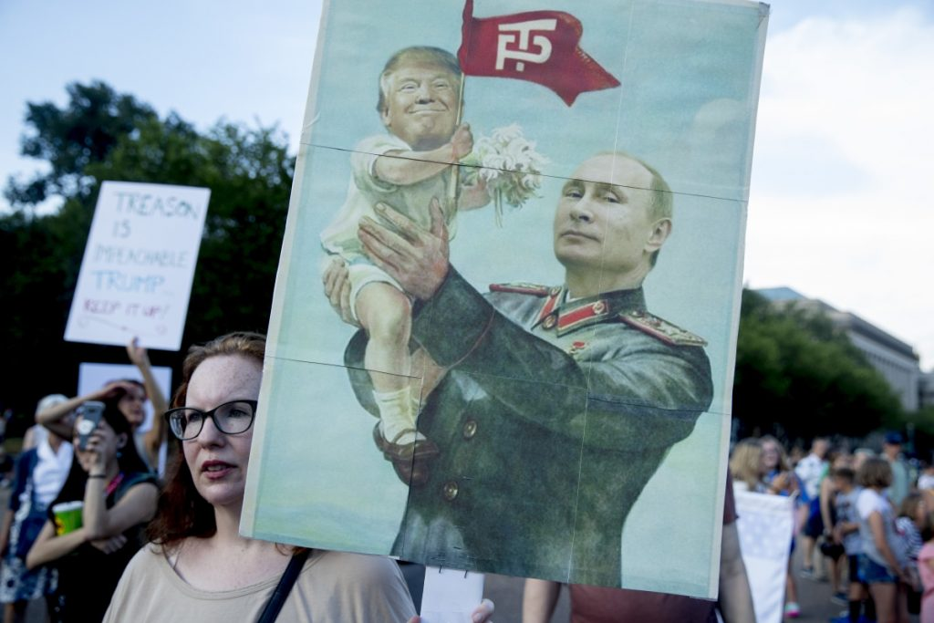 A woman holds a sign depicting Russian President Vladimir Putin and President Trump outside the White House in July.
