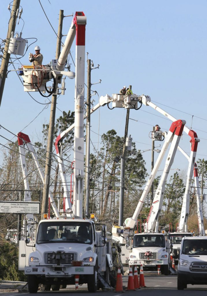 Gulf Power crews line the street in Panama City, Fla., on Friday as they try to restore power after tens of thousands were left without electricity by Hurricane Michael.