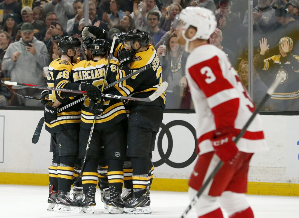Bruins players surround David Pastrnak after one of his two second-period goals on Saturday as Red Wings defenseman Nick Jensen looks up at the replay. Boston won 8-2 at home.