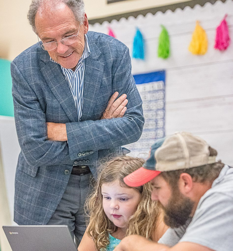 David Roux peeks over the shoulders of Audrey and Scott Scanlon, who are busy coding for Minecraft during Wednesday's Learn-to-Code night at Montello Elementary School in Lewiston.