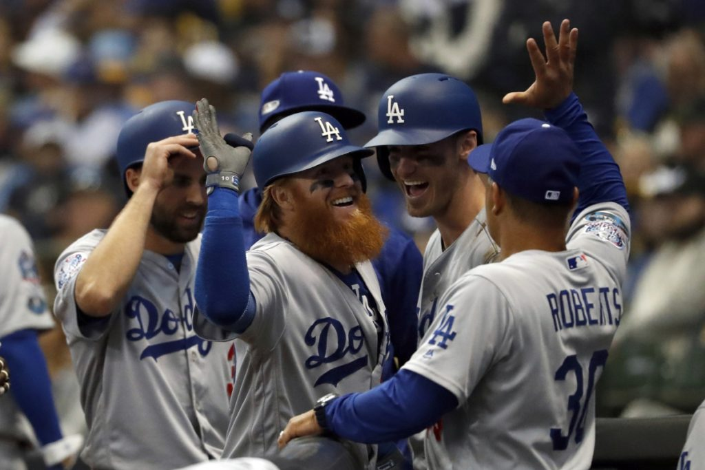 Dodgers sluggers Justin Turner, center, celebrates with Manager Dave Roberts, right, and teammates after hitting a go-ahead, two-run home run during the eighth inning of Game 2 of the NLCS against Milwaukee on Saturday. (AP Photo/Jeff Roberson)