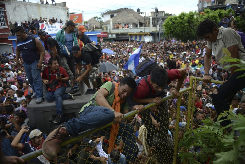 Thousands of Honduran migrants rush across the border towards Mexico, in Tecun Uman, Guatemala, Friday, Oct. 19, 2018. Migrants broke down the gates at the border crossing and began streaming toward a bridge into Mexico. After arriving at the tall, yellow metal fence some clambered atop it and on U.S.-donated military jeeps. Young men began violently tugging on the barrier and finally succeeded in tearing it down. (AP Photo/Oliver de Roos)