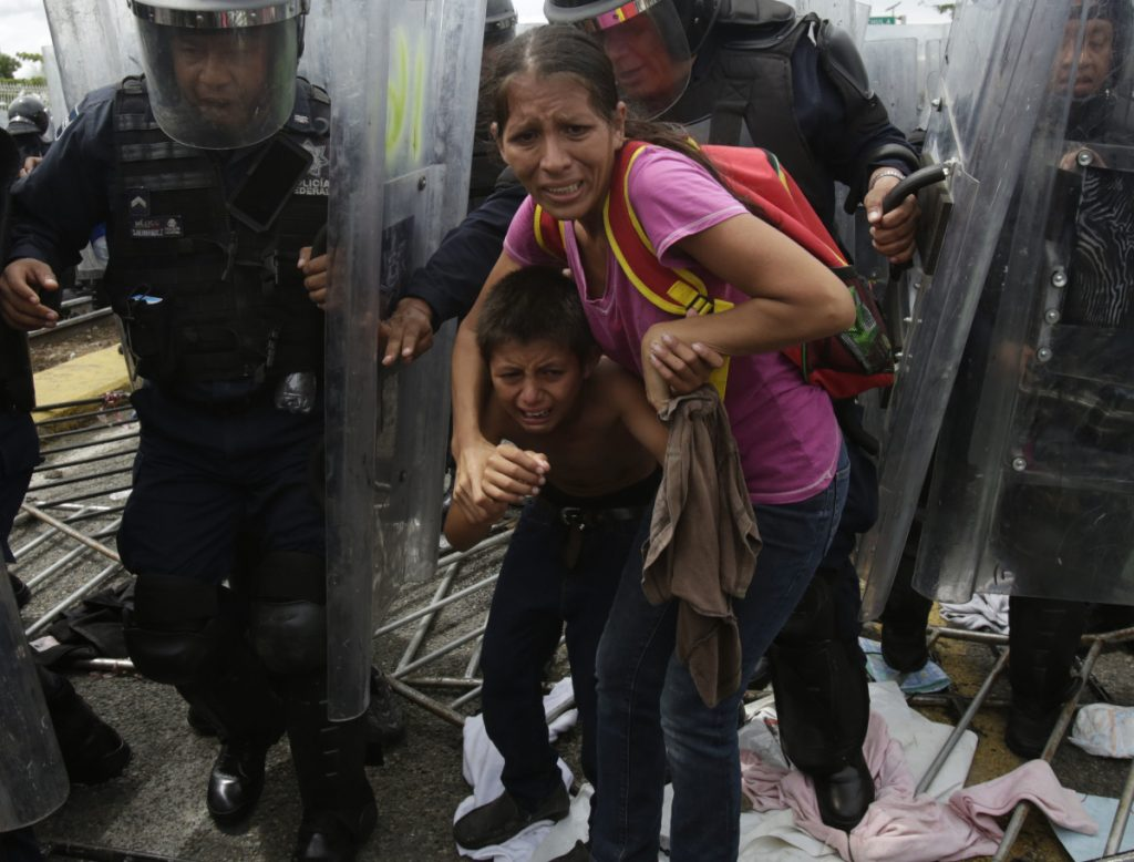 A Honduran migrant mother and her son are shielded by Mexican Federal Police from stones thrown by unidentified people at the border crossing in Ciudad Hidalgo, Mexico, on Friday.