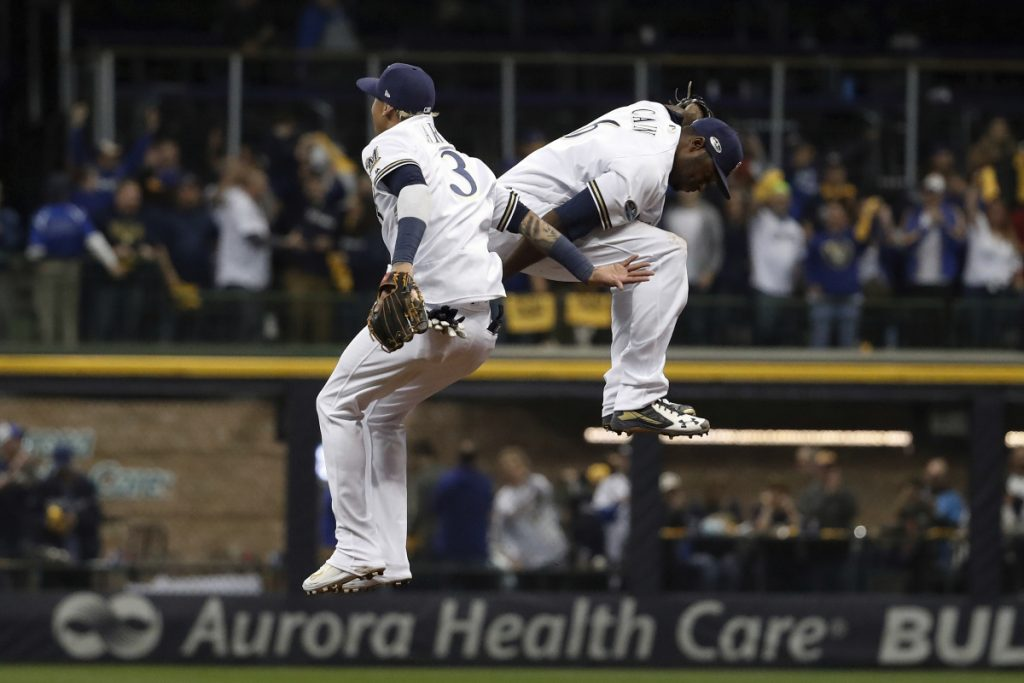 Milwaukee's Orlando Arcia (3) and Lorenzo Cain celebrate after Game 6 of the National League Championship Series against the Los Angeles Dodgers on Friday night in Milwaukee. The Brewers won 7-2.