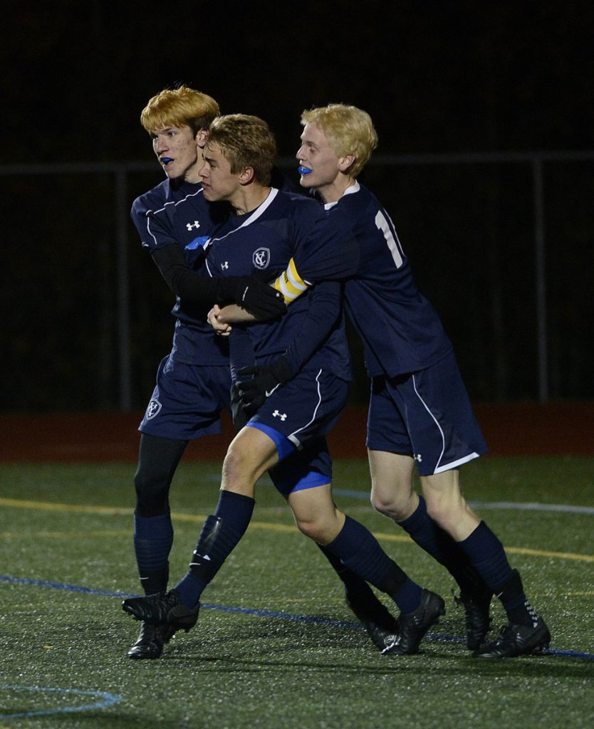 Yarmouth's Aidan Hickey, center, is swarmed by teammates Eric LaBrie, left, and Jack Jones after Hickey scored the game's first goal Tuesday.