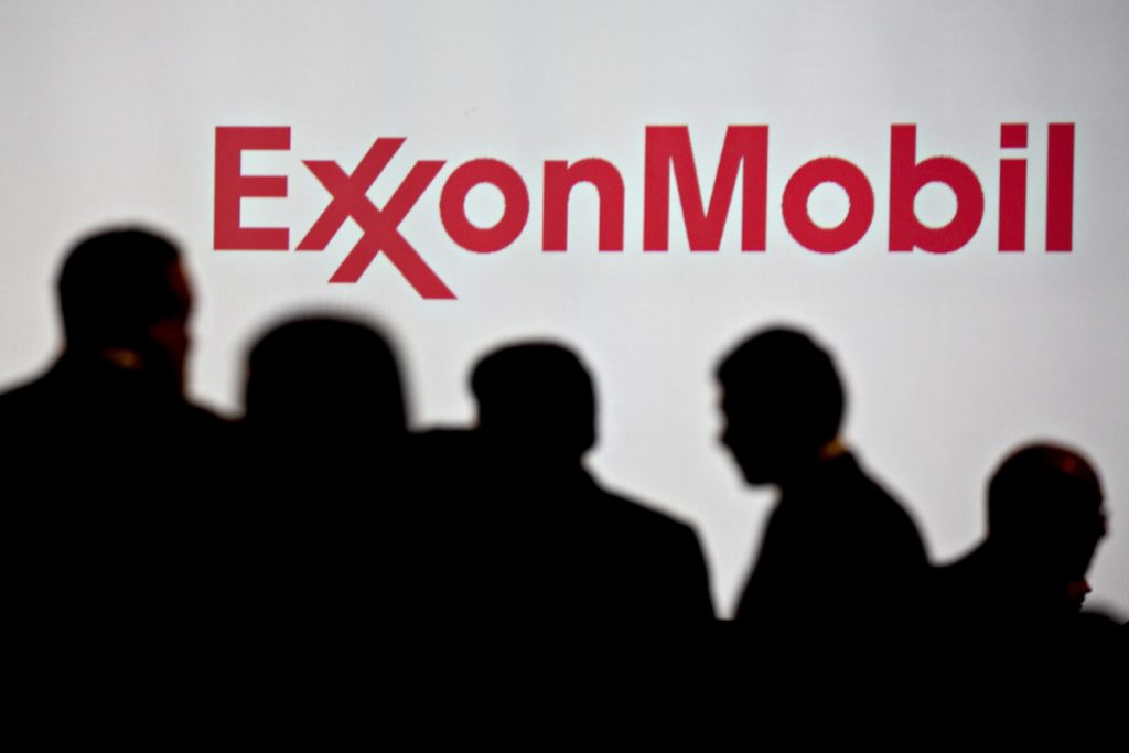 Attendees stand near Exxon Mobil Corp. signage during a conference in Washington, D.C., on Tuesday, June 26, 2018. Bloomberg/Andrew Harrer