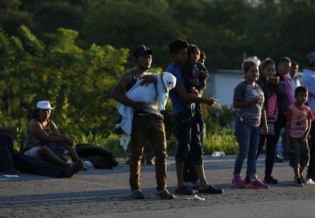 Central American migrants try to hitch rides on passing trucks near Mapastepec, Mexico, on Thursday as thousands head north hoping to reach the U.S. border, still over 1,000 miles away.