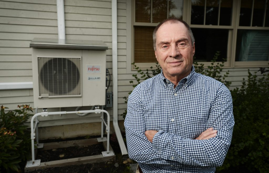 Mark Peterson outside his home in Saco with his exterior heat pump unit in the background. Peterson had three heat pump units and a heat-pump water heater installed two years ago and has not saved money or had better heating.