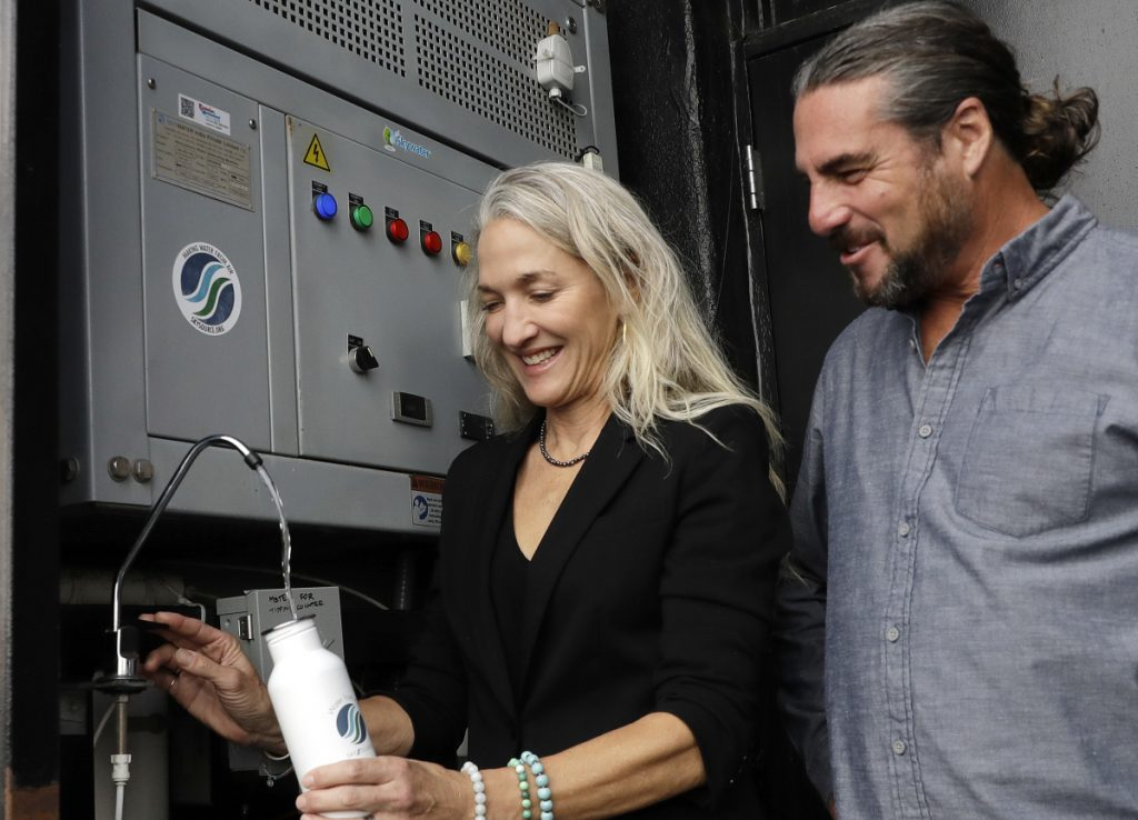 Skysource/Skywater Alliance co-founders David Hertz, right, and his wife, Laura Doss-Hertz, demonstrate the Skywater 300, a machine that makes water from air, in Los Angeles this week.