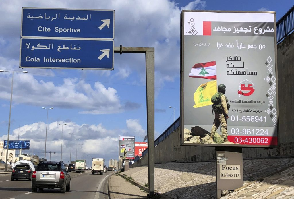 Billboards from Hezbollah's committee for the support of the Islamic resistance, that shows a Hezbollah fighter while holding the group's yellow banner and the Lebanon's national flag, are displayed on the Beirut airport highway in January.