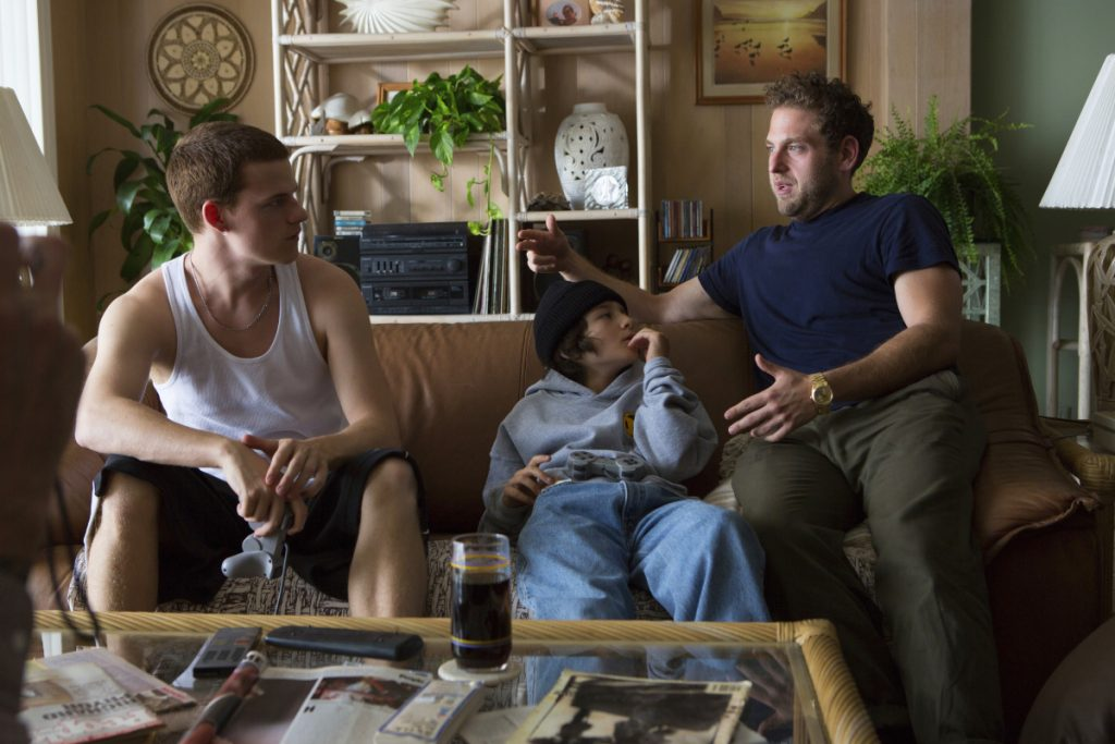 """This image released by A24 shows writer-director Jonah Hill, right, with cast members Lucas Hedges, left, and Sunny Suljic during the filming of """"Mid90s."""""""