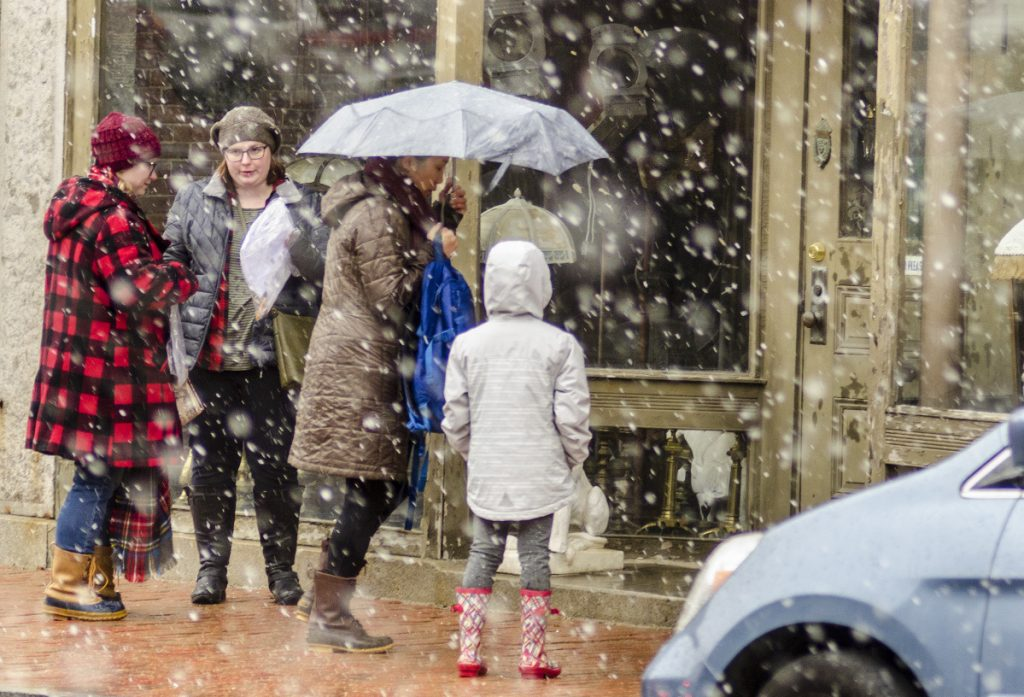 People walk through a flurry of wet snow Saturday on Water Street in Hallowell. It was the start of a nor'easter that blew through over the weekend.