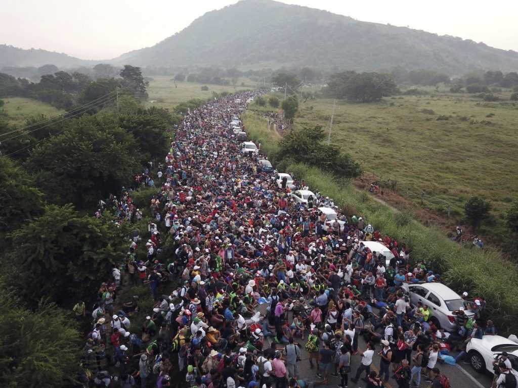 Members of a U.S.-bound migrant caravan stand on a road after federal police briefly blocked their way outside the town of Arriaga on Saturday. Hundreds of Mexican federal officers carrying plastic shields had blocked the caravan from advancing toward the United States, after several thousand of the migrants turned down the chance to apply for refugee status and obtain a Mexican offer of benefits. Associated Press/Rodrigo Abd