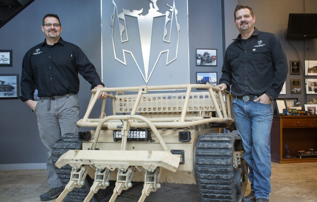 Brothers Michael, left, and Geoffrey Howe pose with their robot vehicle at their business in Waterboro. The company is growing, thanks to a major influx of capital from a defense industry giant.