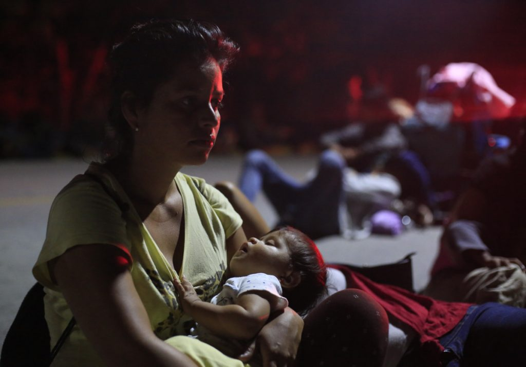A woman holding her sleeping baby waits in hopes of hitching a ride, as a thousands-strong caravan of Central Americans continues its slow march toward the U.S. border, in Tapanatepec, Oaxaca state, Mexico, before dawn on Monday. Thousands of migrants traveling together for safety resumed their journey after taking a rest day Sunday, while hundreds more migrants were pushing for entry to Mexico.
