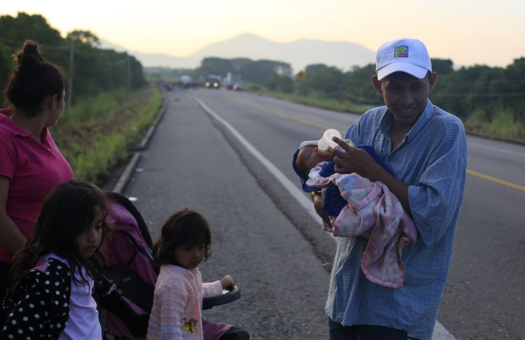 Guatemalan migrant Ernesto Cayax, 27, feeds his 25-day-old baby daughter, Reychel, as he takes a break from walking with his wife, Jahana Estrada, 23, and their three children, on the roadside outside Tapanatepec, Mexico, before dawn on Monday. The family joined up seven days ago with a thousands-strong caravan of Central Americans trying to reach the U.S. border, roughly 1000 miles away.