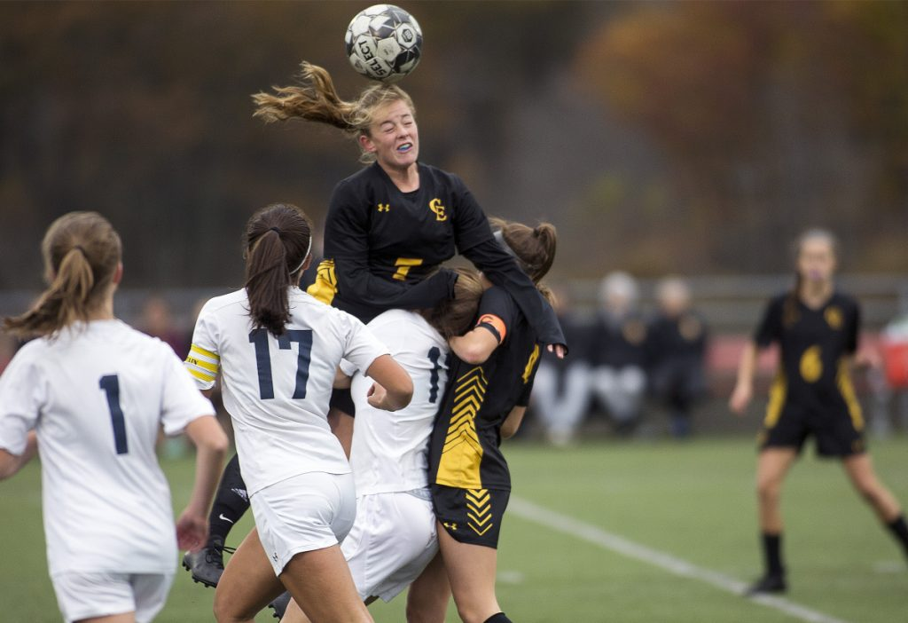 Cape Elizabeth's Karli Chapin, center, jumps over a group of players for a header during the Class B South semifinal against Yarmouth on Monday. Chapin had an assist and the Capers won 2-1.