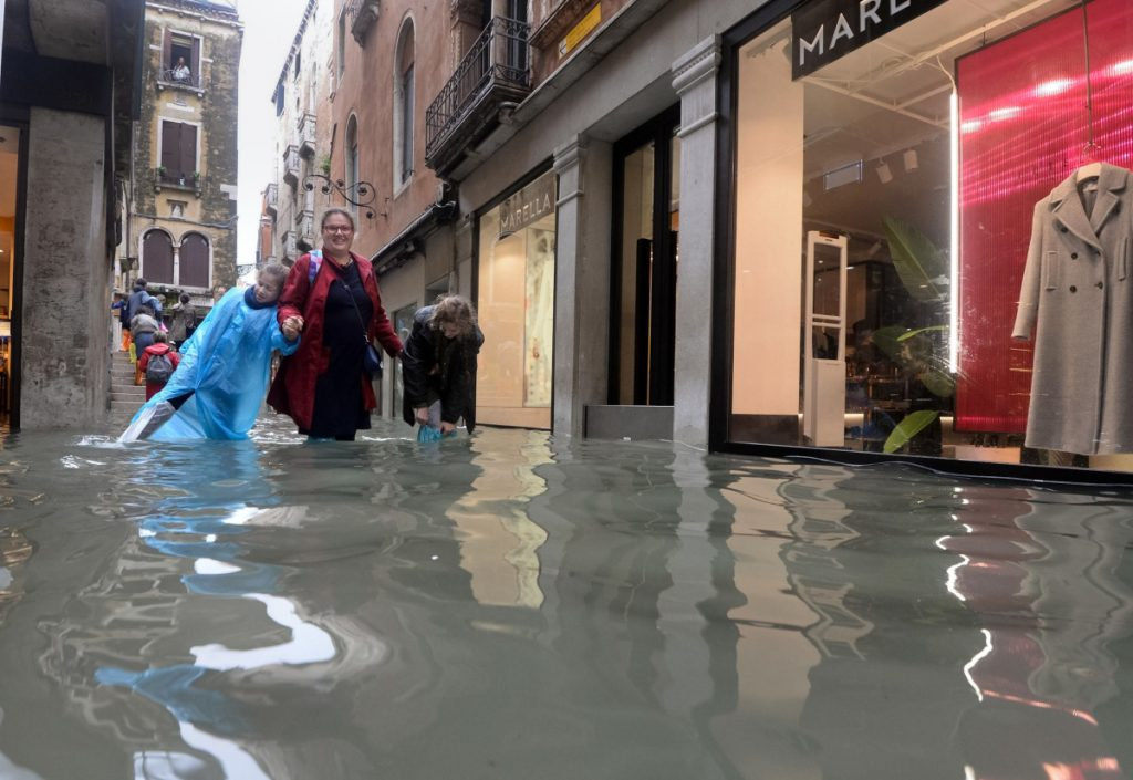 People walk in a flooded street of Venice, Italy, on Monday, as 70 percent of the lagoon city was flooded by waters rising more than five feet above sea level, according to city officials.