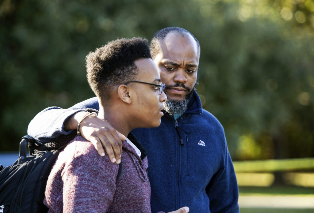 """Gavriel Fulcher-Daniels, left, and Stephen Daniels talk with members of the media after a deadly shooting at Butler High School in Matthews, N.C., Monday. """"It sounded like a balloon but louder,"""" Fulcher-Daniels said, after hearing a gunshot."""