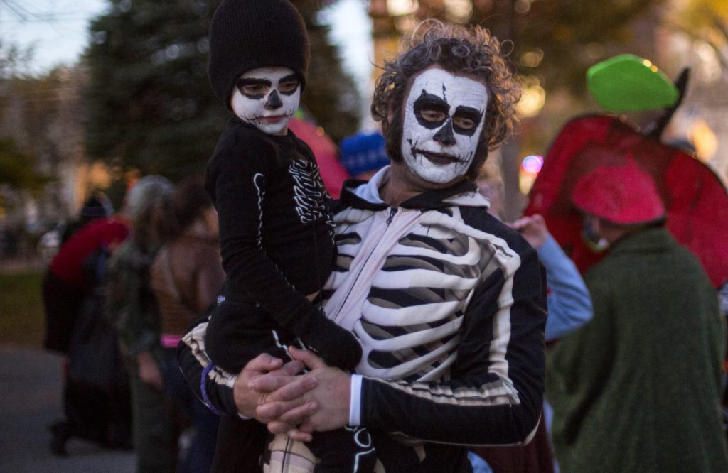 Michael Gatlin and his son Ovid, 5, await the start of the Halloween parade on Brackett Street in Portland last year.