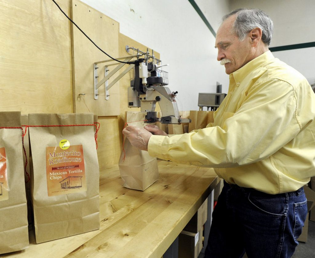 In this file photo from 2010, Scott Rehart, owner of Montecito Roadhouse Inc. in Portland, stitches a bag of tortilla chips.