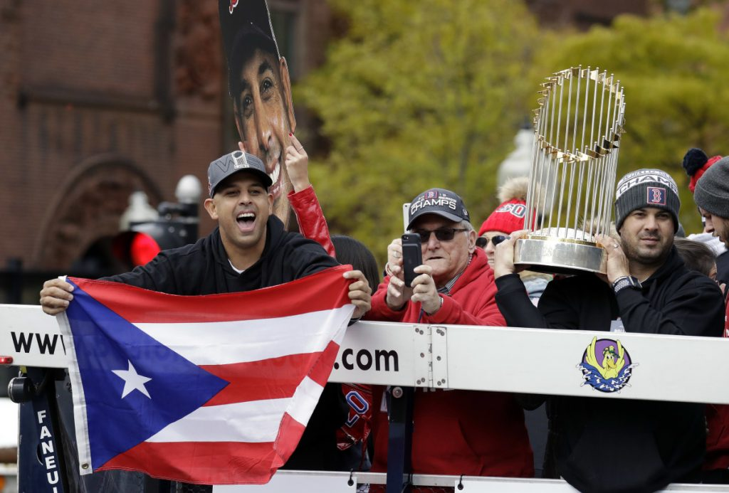 Boston Red Sox manager Alex Cora, left, waves the flag of Puerto Rico as coach Ramon Vazquez holds the championship trophy during a parade to celebrate the team's World Series championship over the Los Angeles Dodgers, Wednesday, Oct. 31, 2018, in Boston. (AP Photo/Elise Amendola)