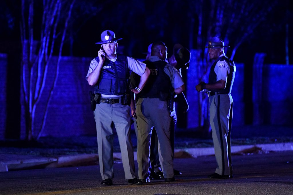 South Carolina state troopers gather Wednesday evening near the neighborhood where seven law enforcement officers were shot, one fatally, in Florence, S.C.