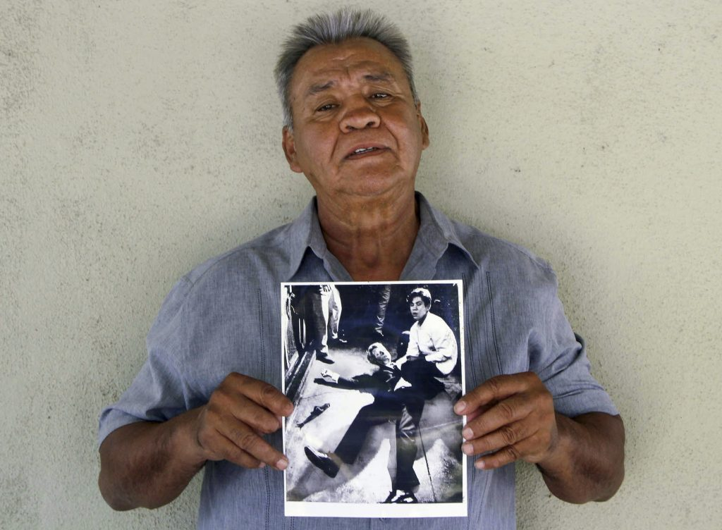 This photo provided by STORYCORPS shows Juan Romero holding a Los Angeles Times photograph that shows Romero with Sen. Robert F. Kennedy at the Ambassador hotel in Los Angeles moments after Kennedy was shot. The Los Angeles Times reported Thursday, Oct. 4, 2018, that Romero died Monday in Modesto, California, at age 68.  Romero was a busboy in June 1968 when Kennedy walked through the Ambassador Hotel kitchen after his victory in the California presidential primary and an assassin shot him in the head. He held the mortally wounded Kennedy as he lay on the ground, struggling to keep the senator's bleeding head from hitting the floor.