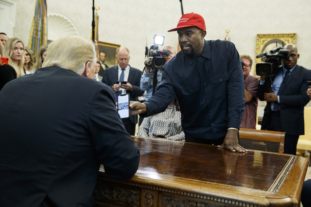 Rapper Kanye West shows President Trump a photograph of a hydrogen plane during a meeting in the Oval Office on Thursday.