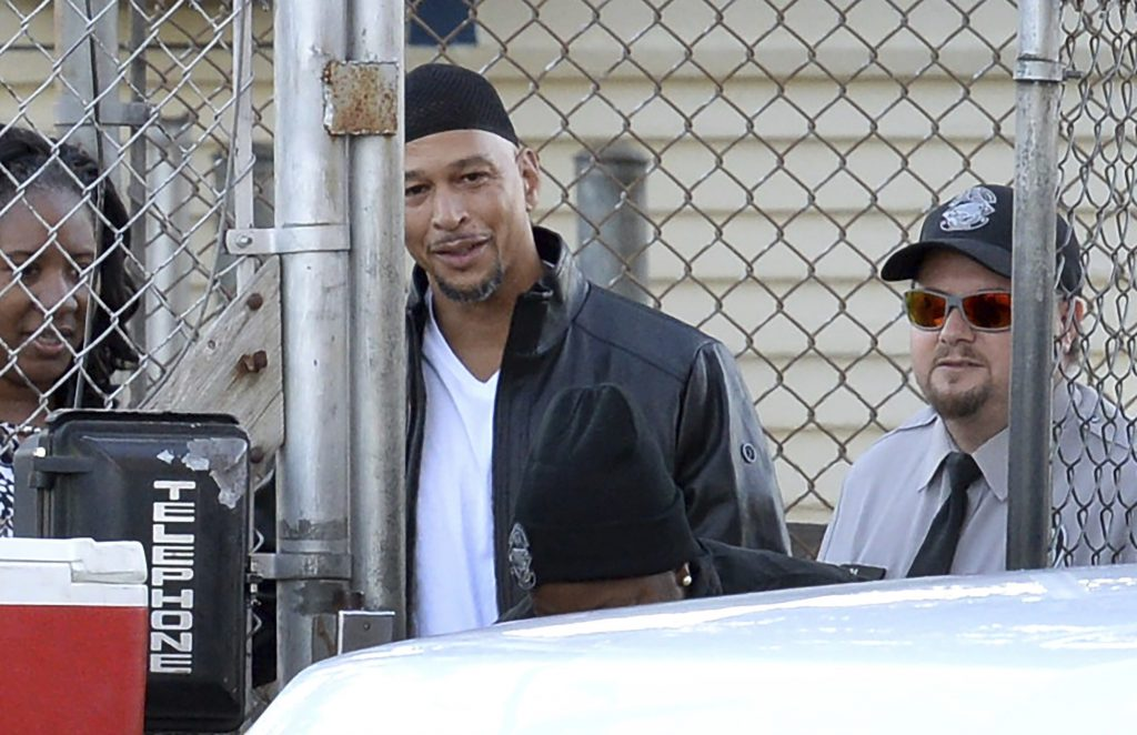 Former Carolina Panthers NFL football player Rae Carruth, center rear, exits the Sampson Correctional Institution in Clinton, N.C., Monday, Oct. 22, 2018. Carruth has been released from prison after serving 18 years for conspiring to murder the mother of his unborn child.
