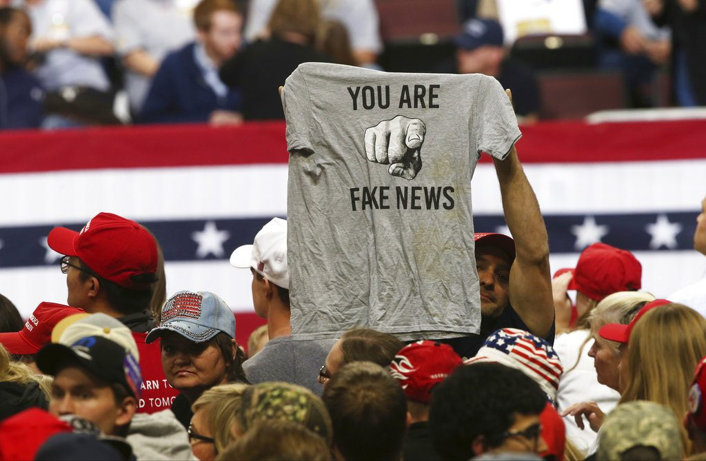 """A Trump supporter holds up a T-shirt reading """"You Are Fake News"""" before a rally by President Donald Trump in Rochester, Minn. on October 4."""