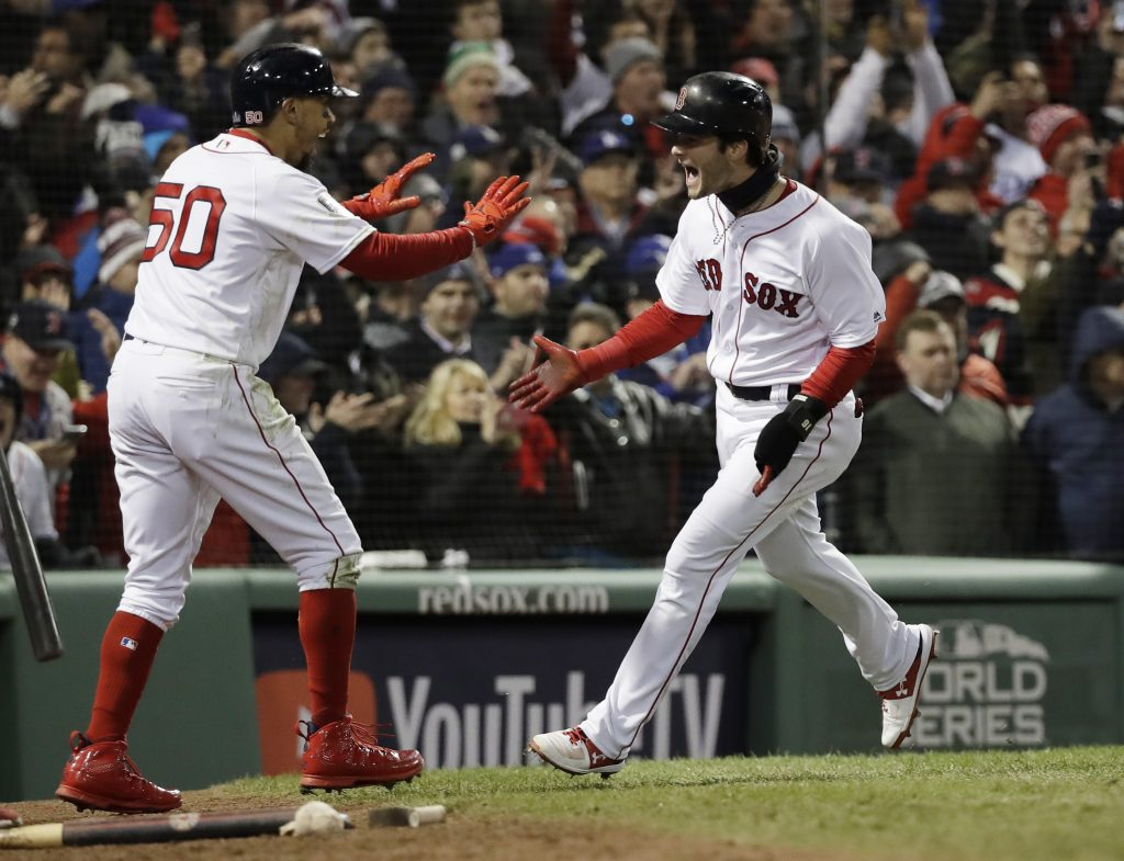 Andrew Benintendi celebrates with Mookie Betts after scoring with Betts on a two-run single by J.D. Martinez in the fifth inning of Game 2 of the World Series on Wednesday night in Boston. The hit proved to be the game winner.