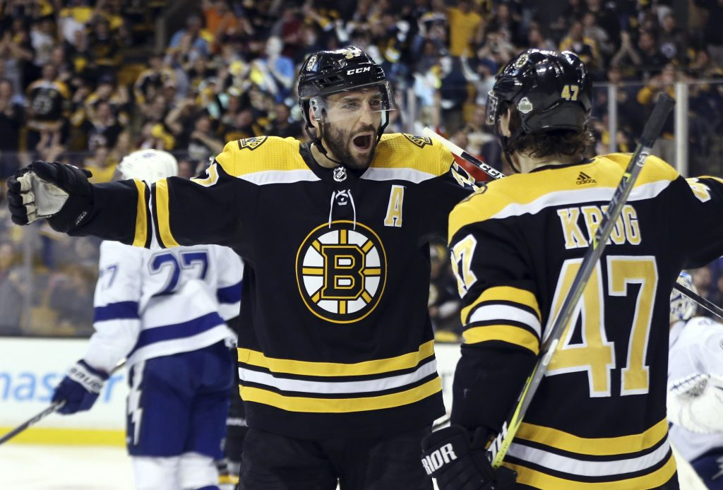 Patrice Bergeron, left, expects to play for the Bruins in their opener Wednesday night, but Torey Krug will not play after suffering a broke left ankle.