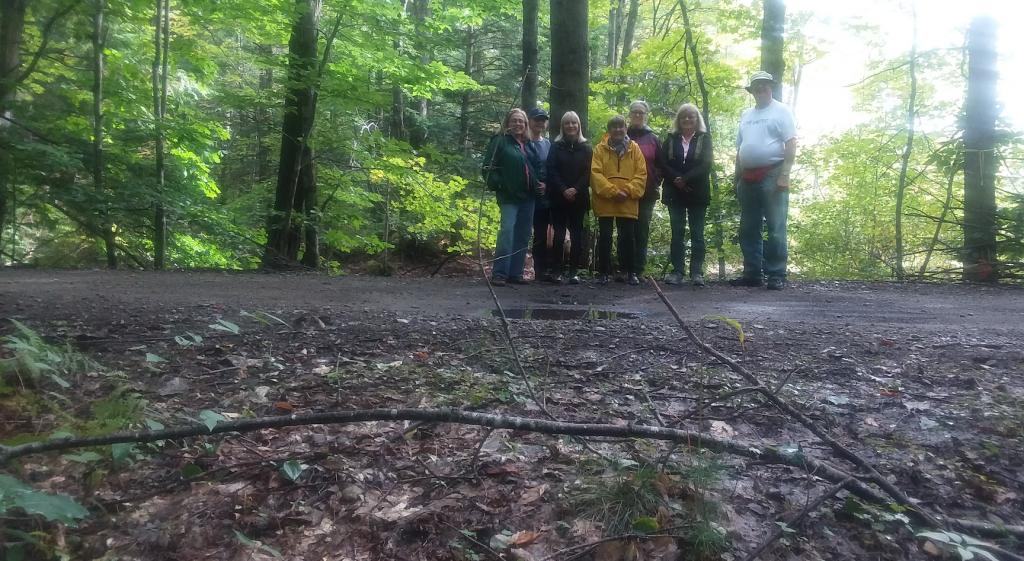 Walkers from the York County Senior College's 'Out in the Woods II' class, hosted by the Mousam Way Land Trust, stand at the end of Deering Pond where a railcar from 1871 went in.